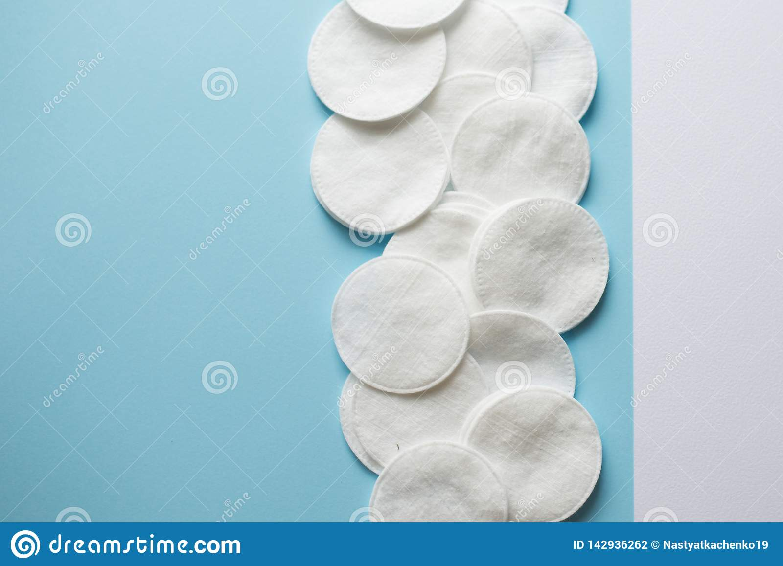 Cotton pads on blue background flat lay.Close-up on group of cotton pads for make up. copy space