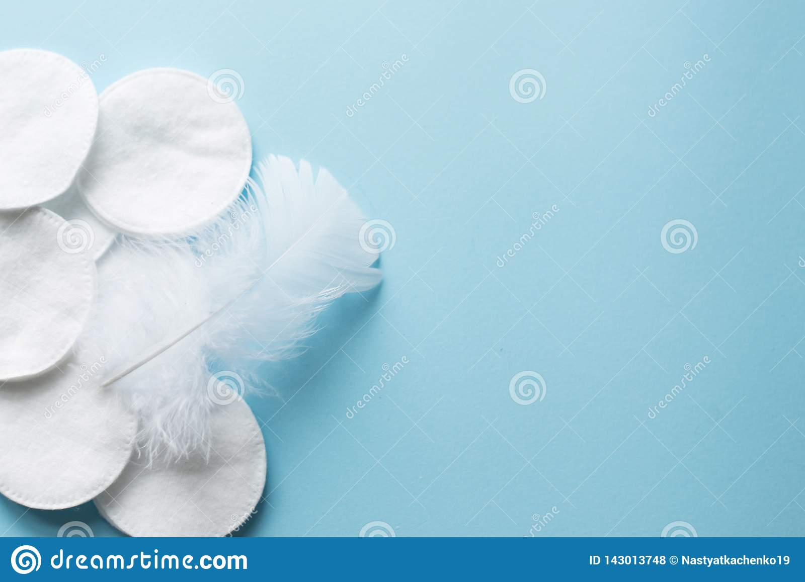 cotton pads with white feather on blue background close up. copy space. top view