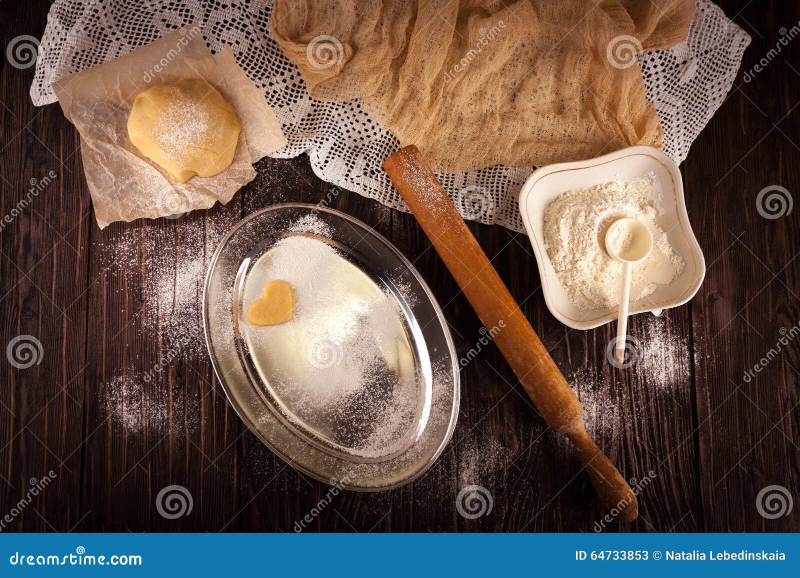 Cottura dei biscotti nel cuore di forma su fondo marrone di legno