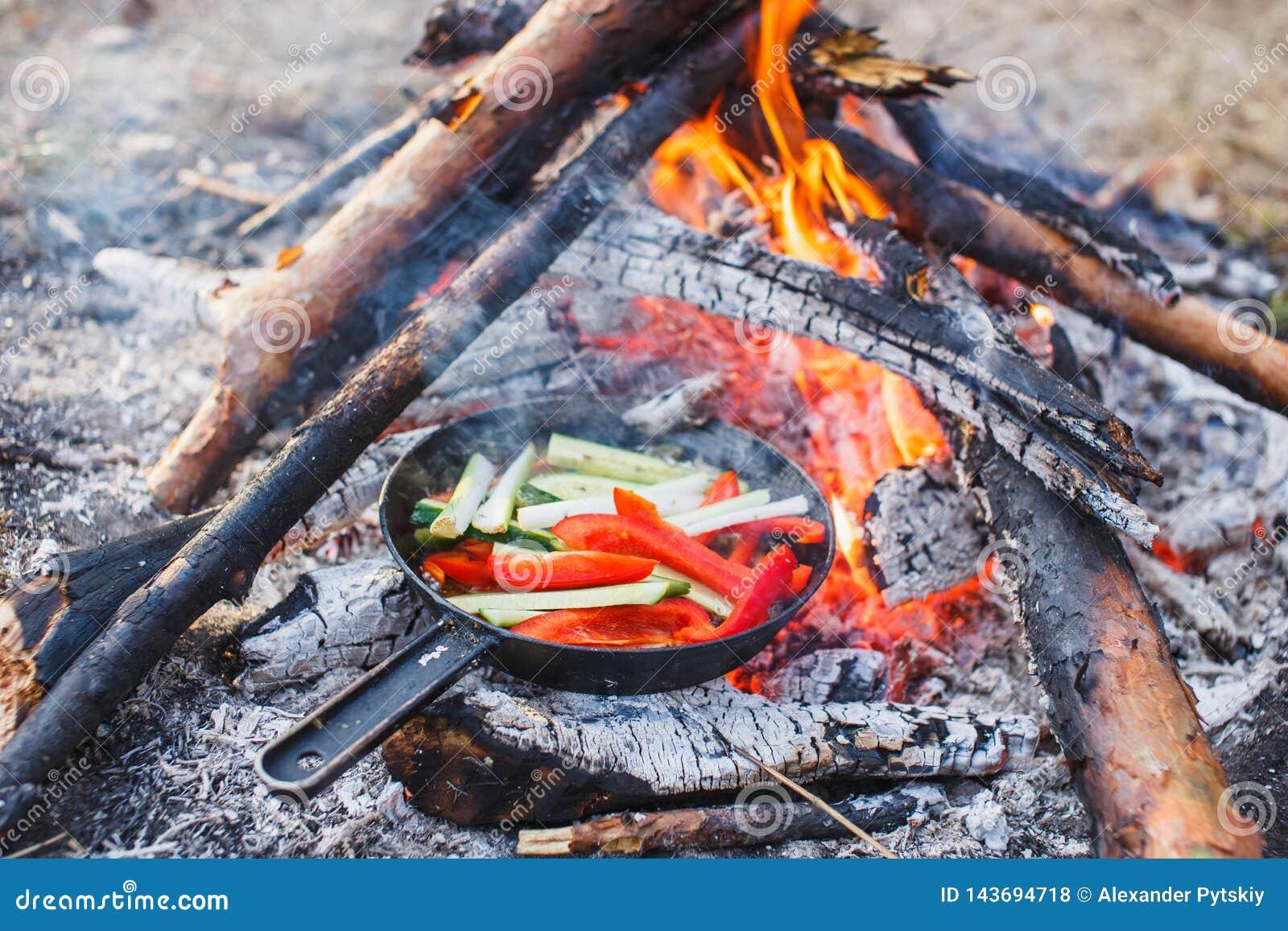 Cottura dei piatti dai peperoni dolci e dai cetrioli rossi in una pentola su un fuoco