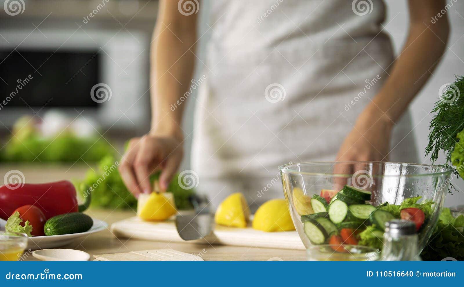 Cottura del dilettante che fa la cucina fresca dell insalata a casa, vestentesi con il succo di limone