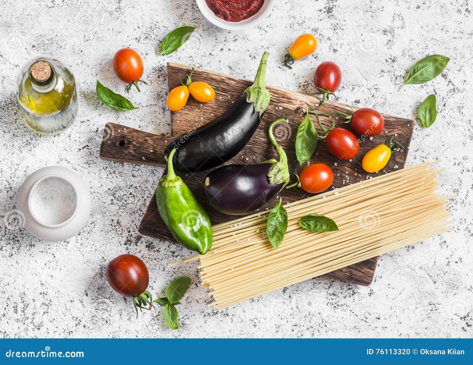 Cottura del fondo Ingredienti crudi per produrre pasta - spaghetti, melanzana, pomodori, pepe, olio d oliva, salsa al pomodoro e