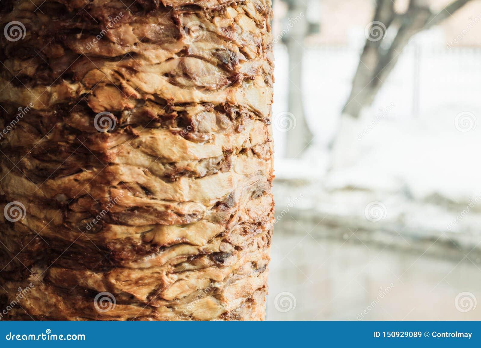 Cottura shawarma e della ciabatta in un caffè Un uomo in carne dei tagli dei guanti eliminabili su uno spiedo