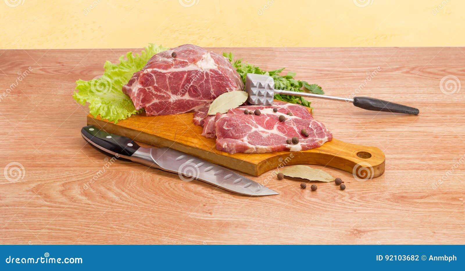 cou de porc sur la planche à découper, l'attendrisseur de viande et