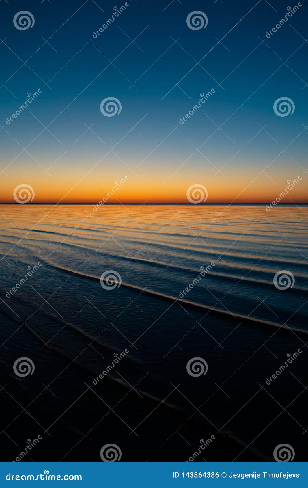 Coucher du soleil étonnant vif dans les pays Baltes - le crépuscule en mer avec l horizon illumine par le soleil