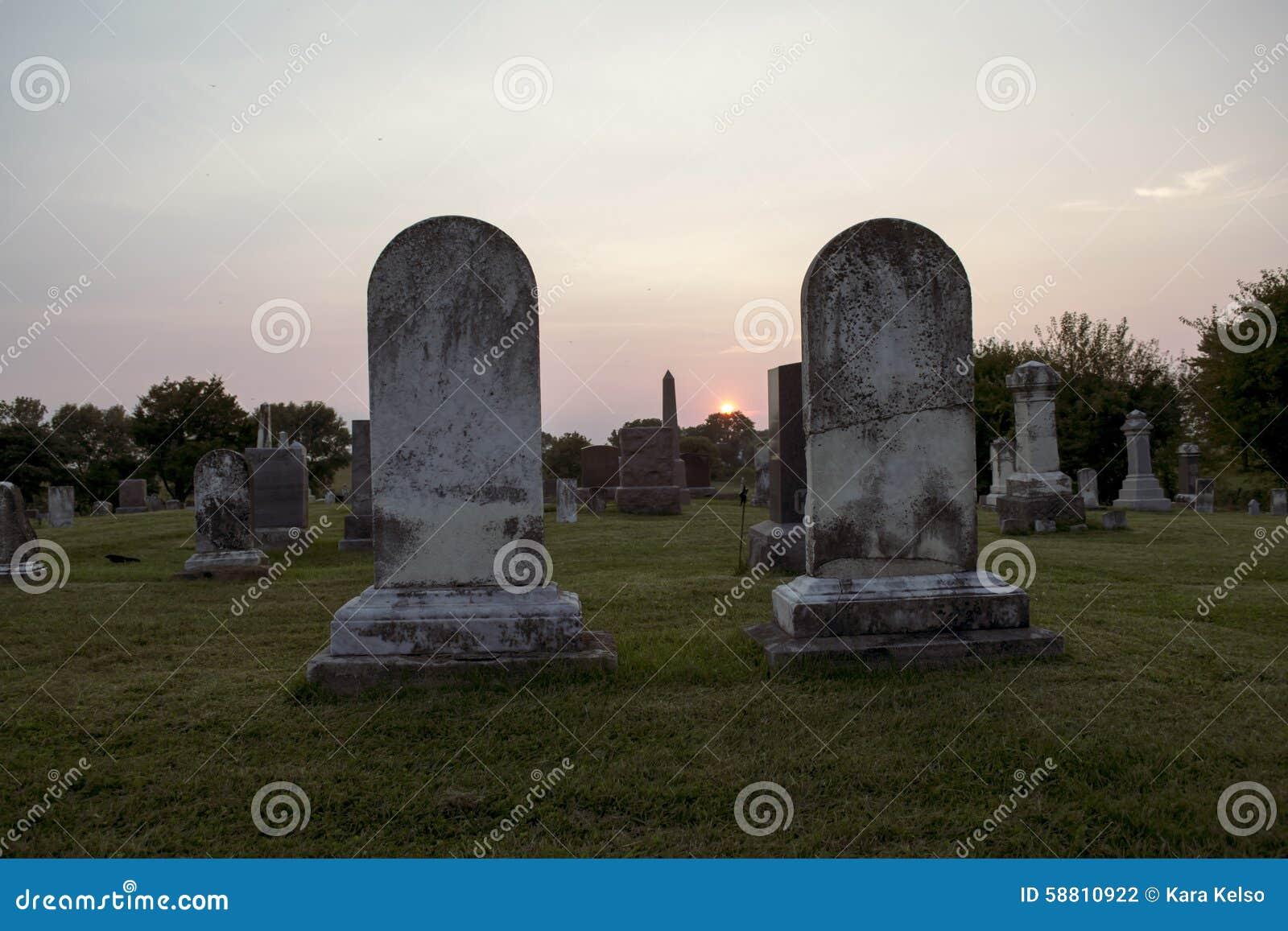 Coucher du soleil au cimetière avec de doubles pierres tombales