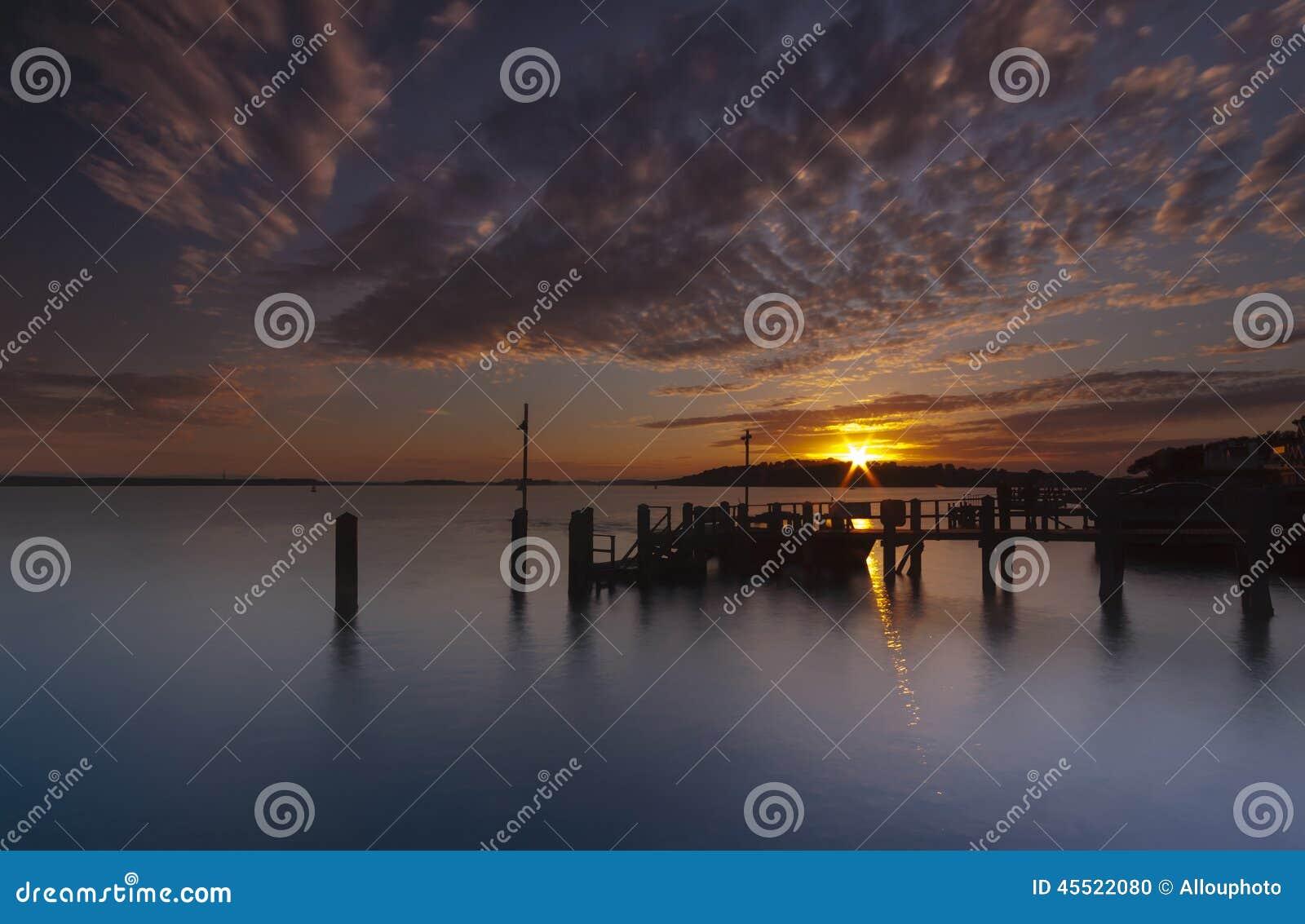 Coucher du soleil au-dessus d une jetée près d île de Brownsea dans le port de Poole