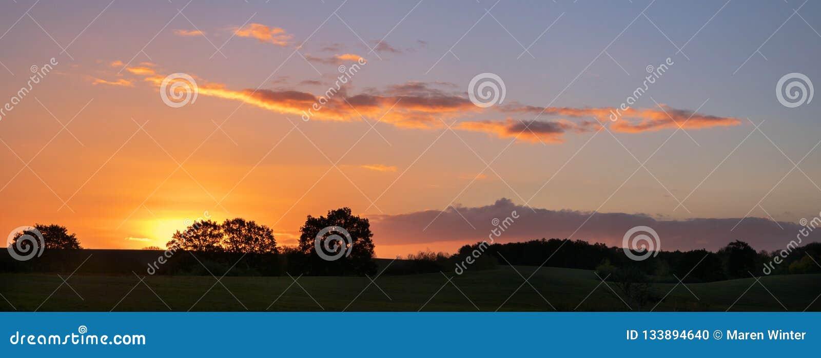 Coucher du soleil avec les nuages oranges au-dessus d un paysage rural large avec le meado