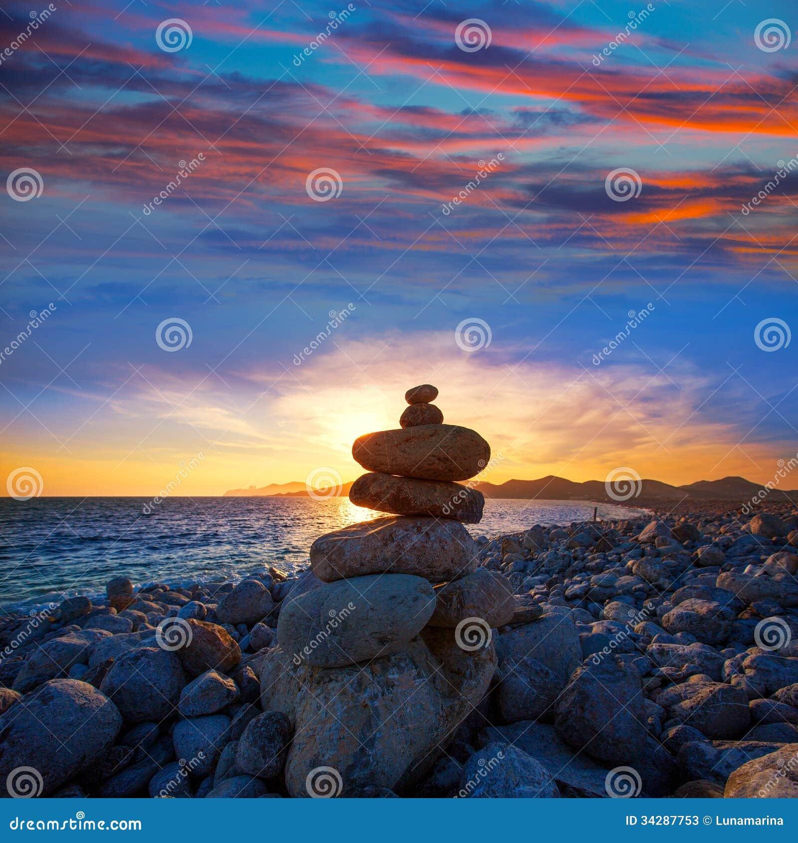 Coucher du soleil de plage de DES Falco de chapeau d Ibiza avec des pierres de désir