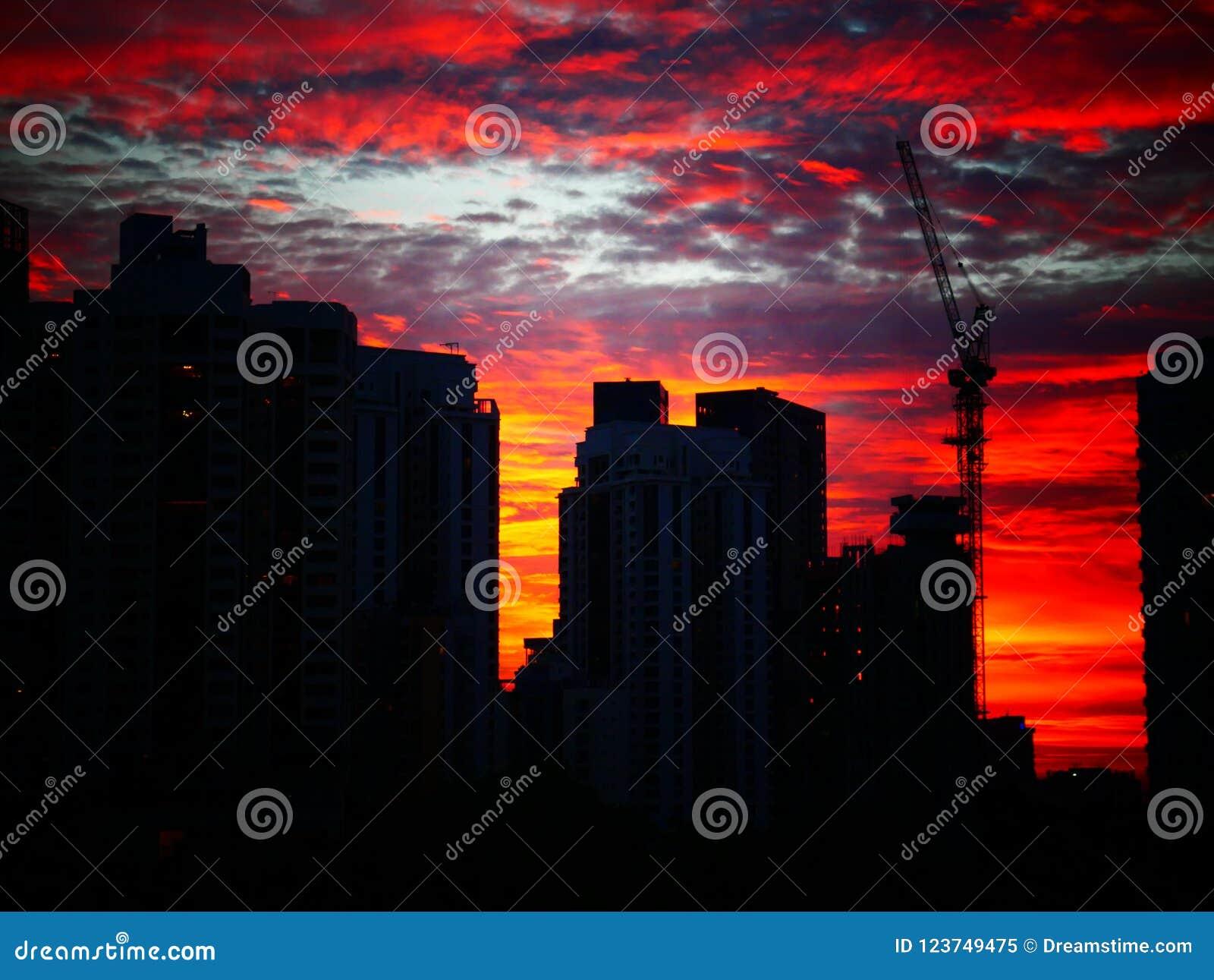 Coucher du soleil derrière des bâtiments avec le beau ciel nuageux