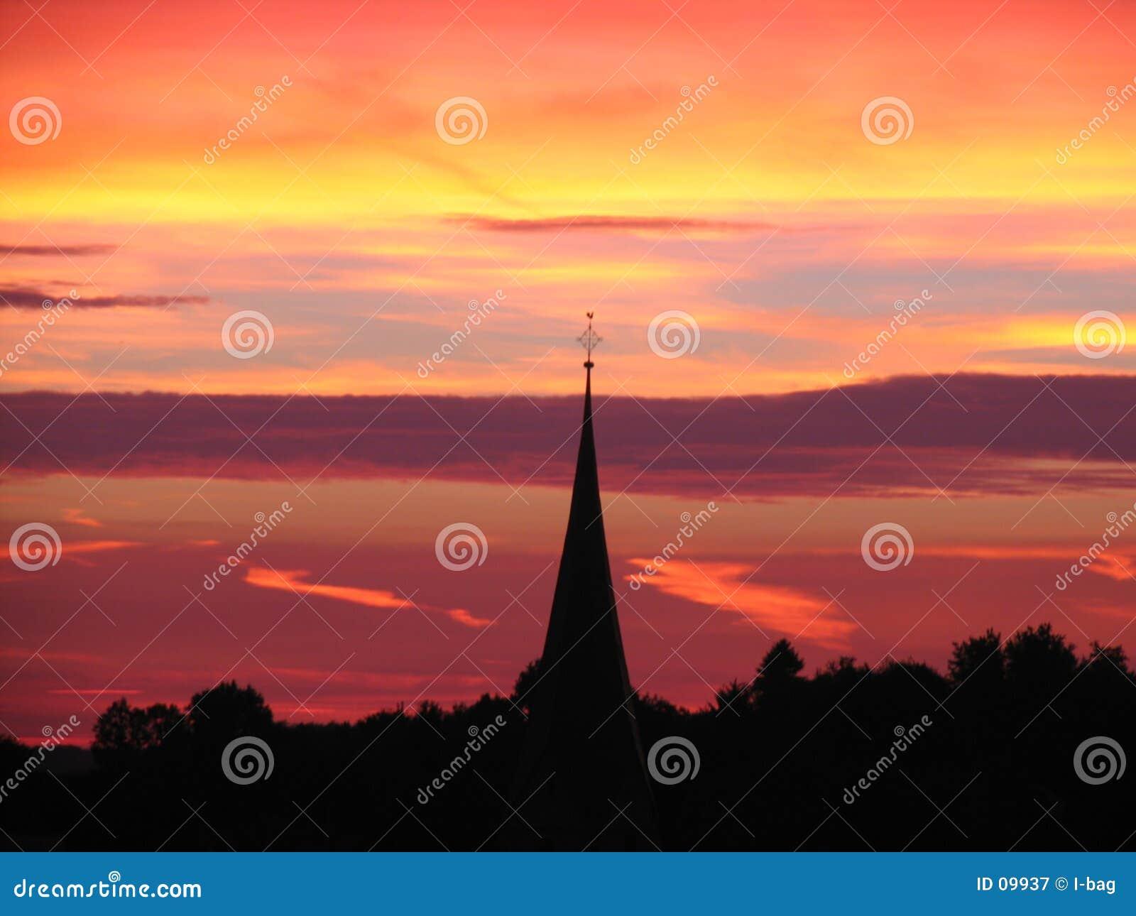 Coucher du soleil derrière la tour d église
