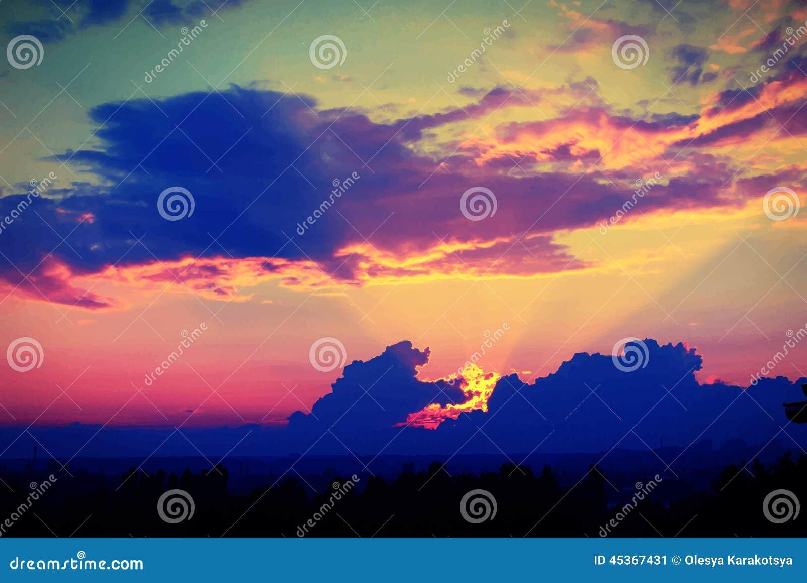 Coucher du soleil merveilleux avec les nuages bleu-foncé, égalisant