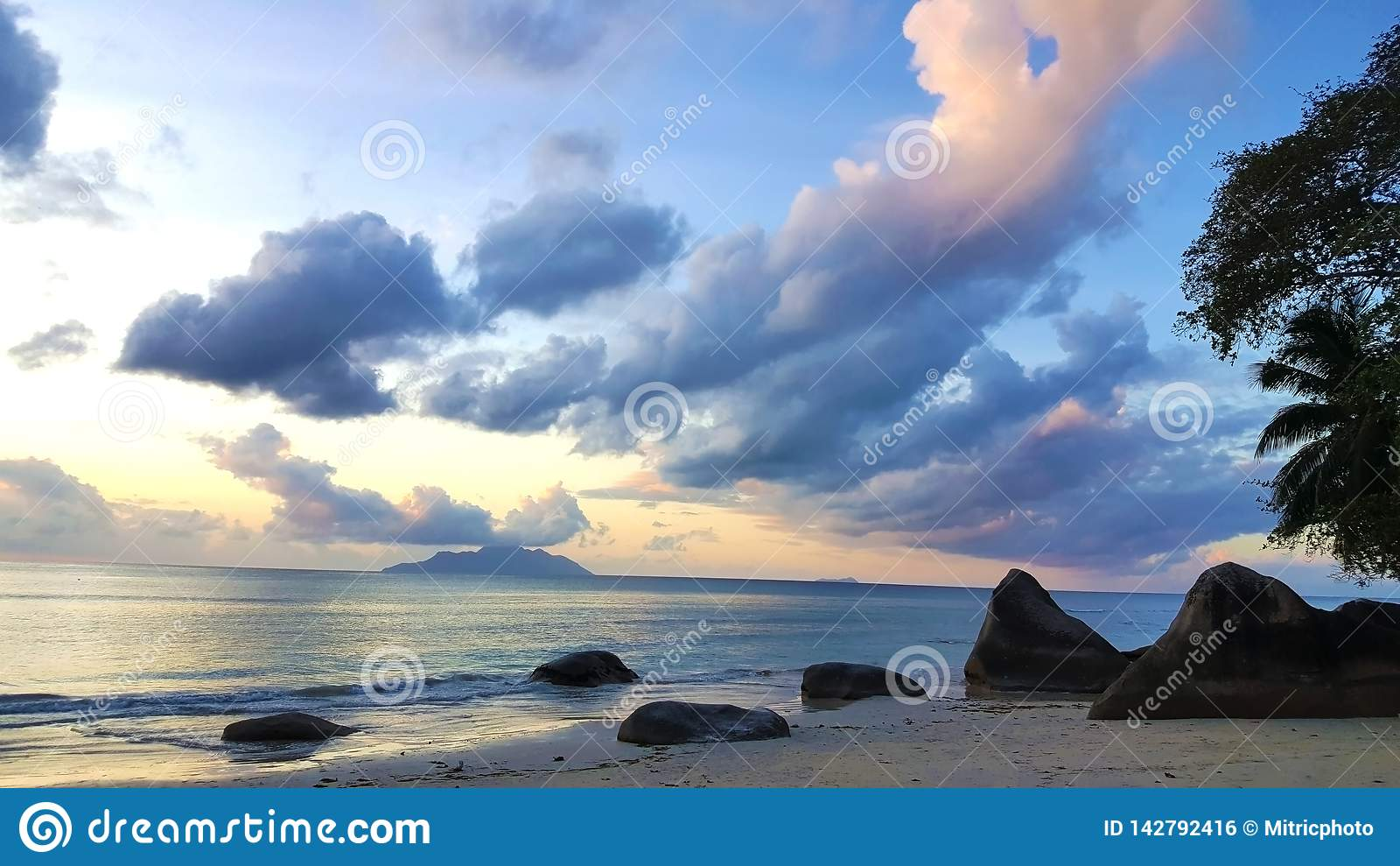 Coucher du soleil paisible de plage des Seychelles avec le ciel et les roches stupéfiants