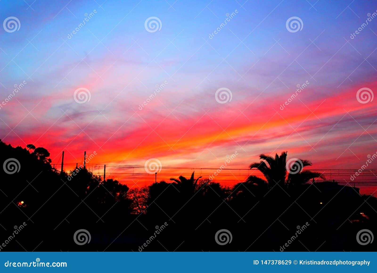 Coucher du soleil pourpre rouge de stupéfaction au-dessus d une ville côtière