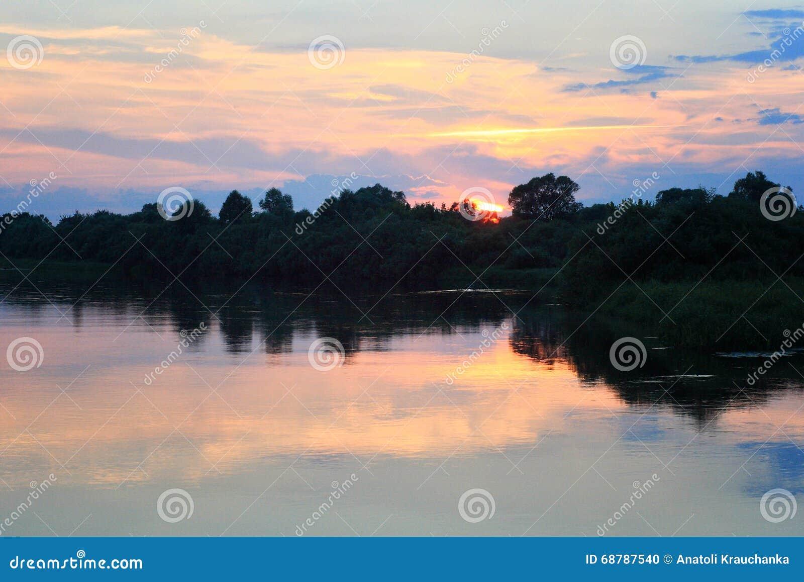 Coucher du soleil rose au-dessus de rivière en été