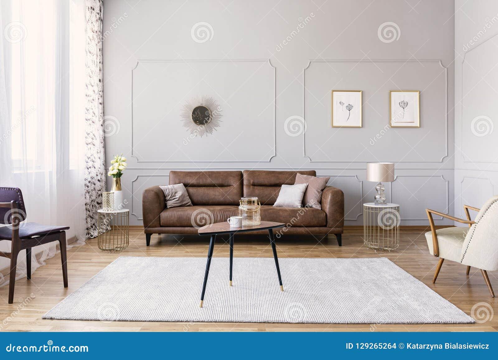 Couchtisch mit Vase und Becher mitten in elegantem Wohnzimmerinnenraum mit bequemem ledernem Sofa, stilvoller purpurroter Stuhl