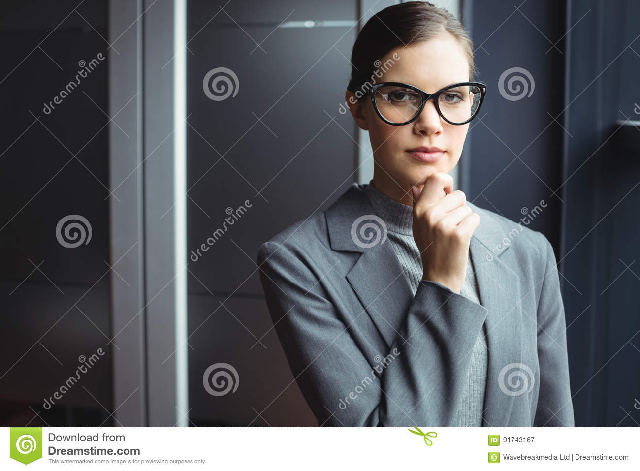 Counselor in glasses with hand on chin