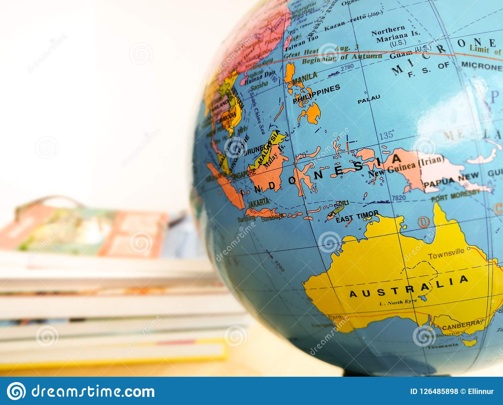 Countries and continents close up with the color map on a globe with books in the background.