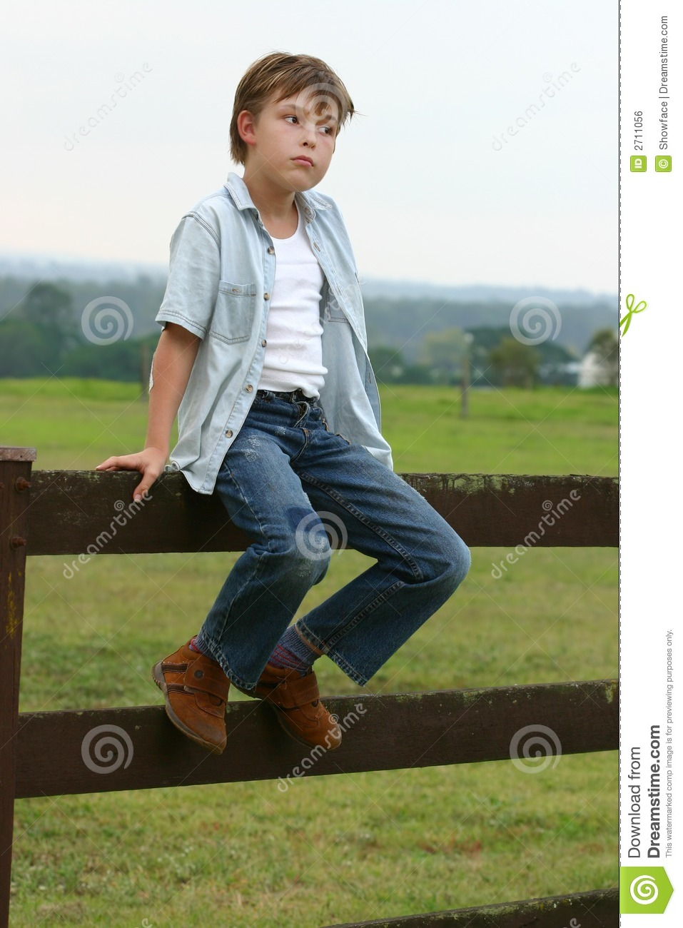 Country boy sitting on a fence