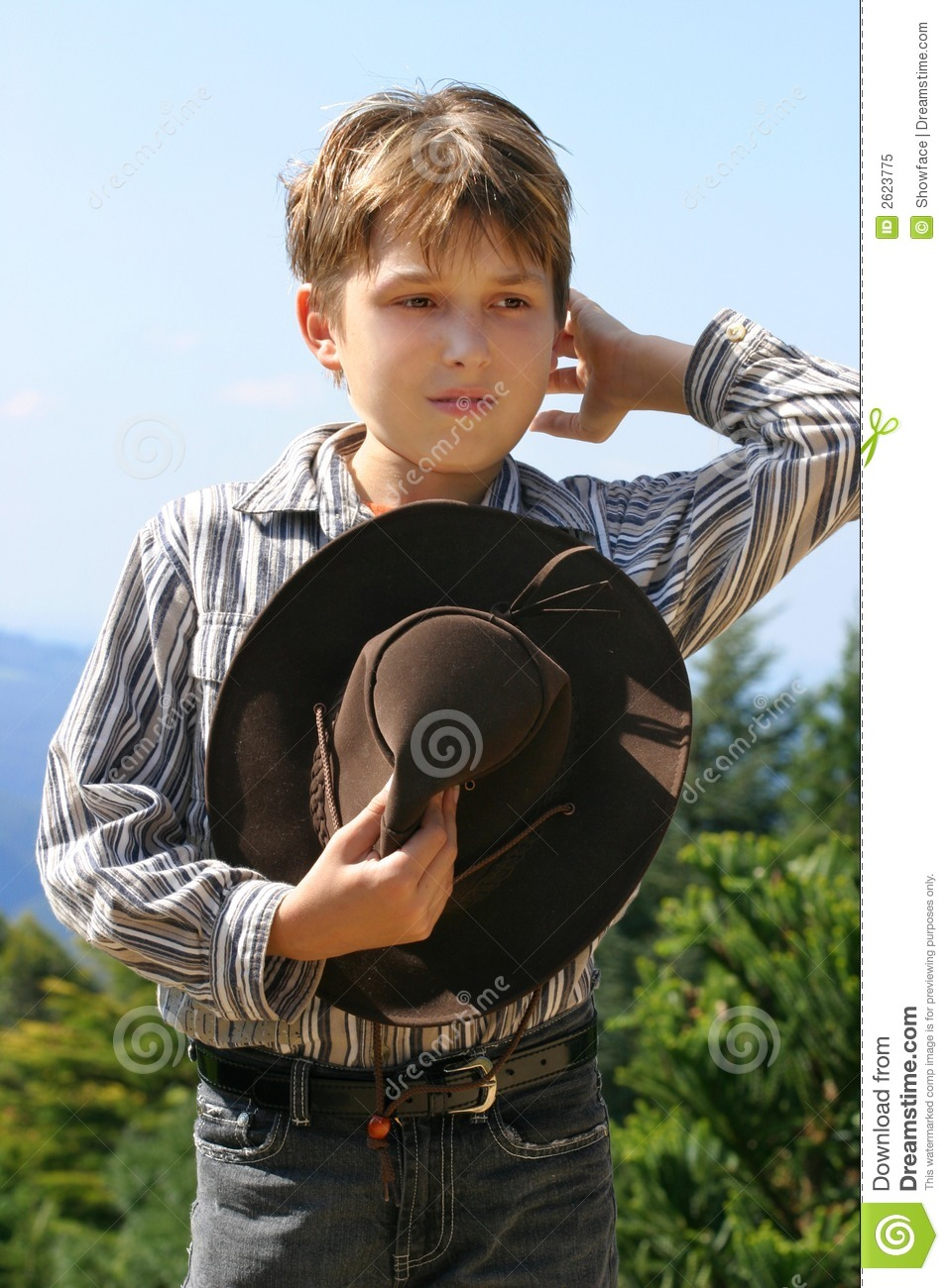 Outback rural boy in magnificent high country, holding hat, whilst ...