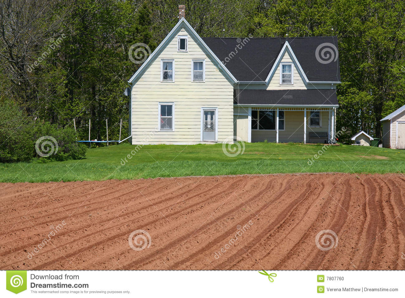 An old country farmhouse with a freshly plowed field in the foreground ...