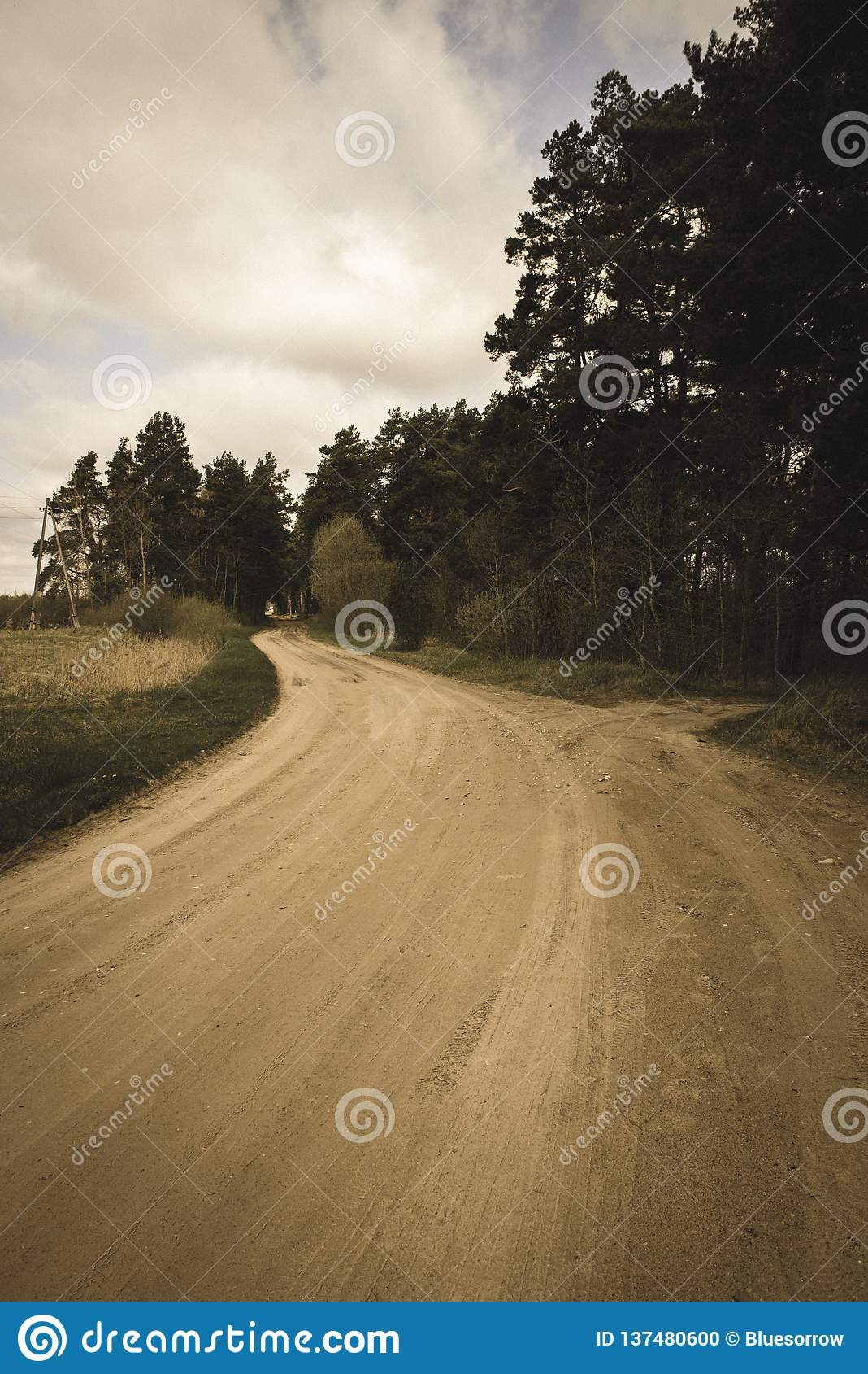 Country gravel road with old and broken asphalt - vintage retro look. Country gravel road in perspective with old and broken asphalt in spring season with poor stock photo
