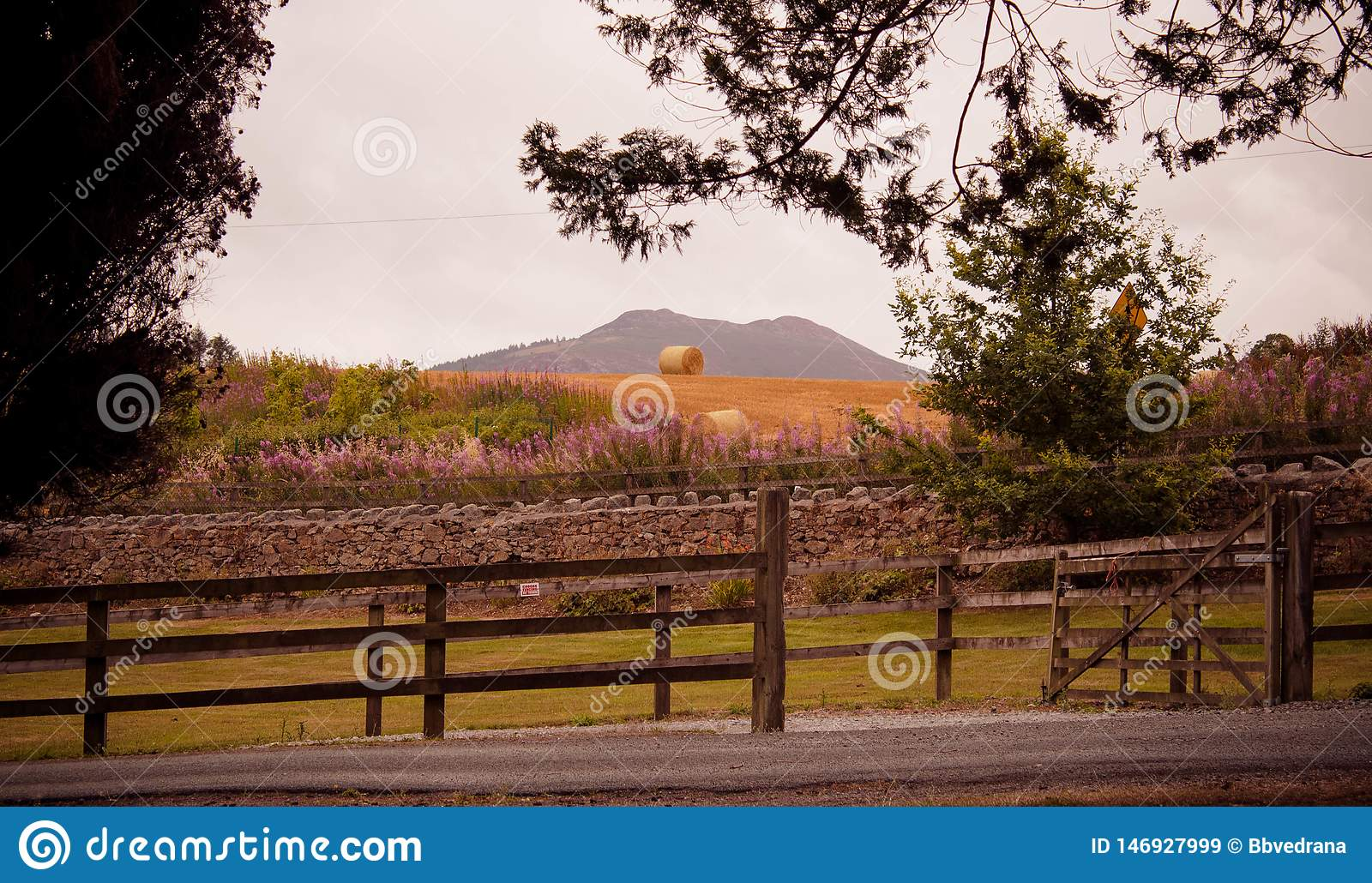 Country hill with wooden fence and bales of hay