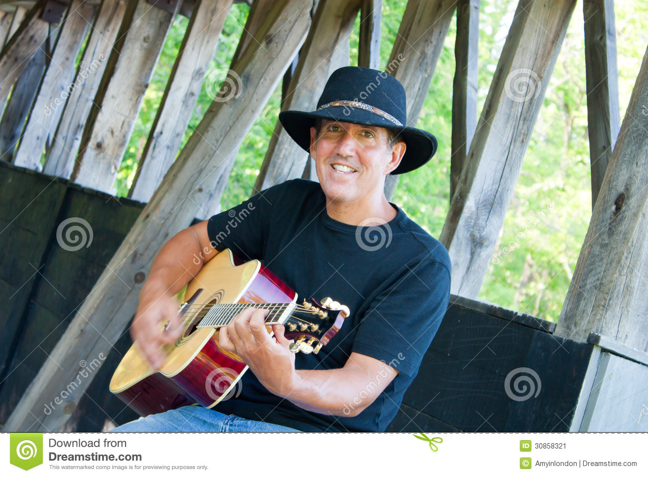 e9e71ec2ab39c A man in jeans and cowboy hat plays guitar at the covered bridge