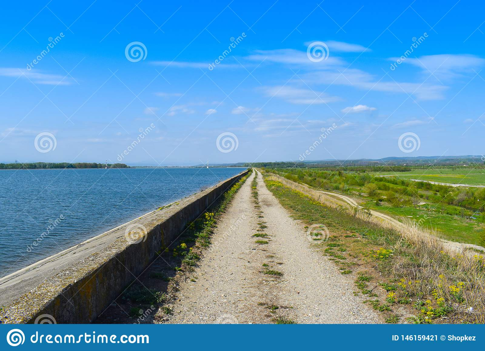 Country road along the lake dam in a sunny summer day with perfect blue sky
