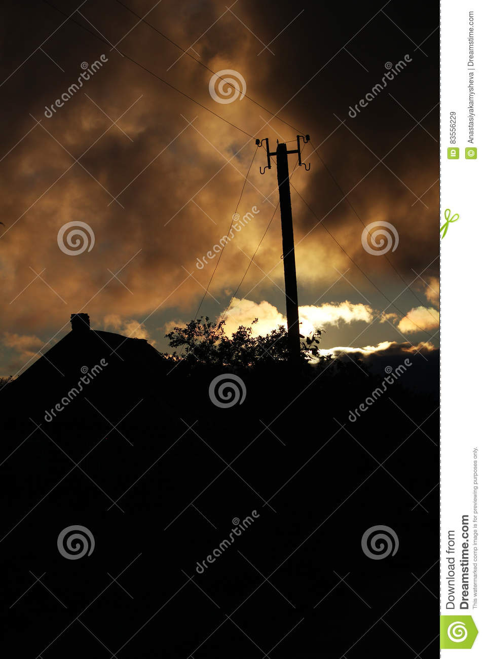 A countryside house roof and an electric line at sunset time