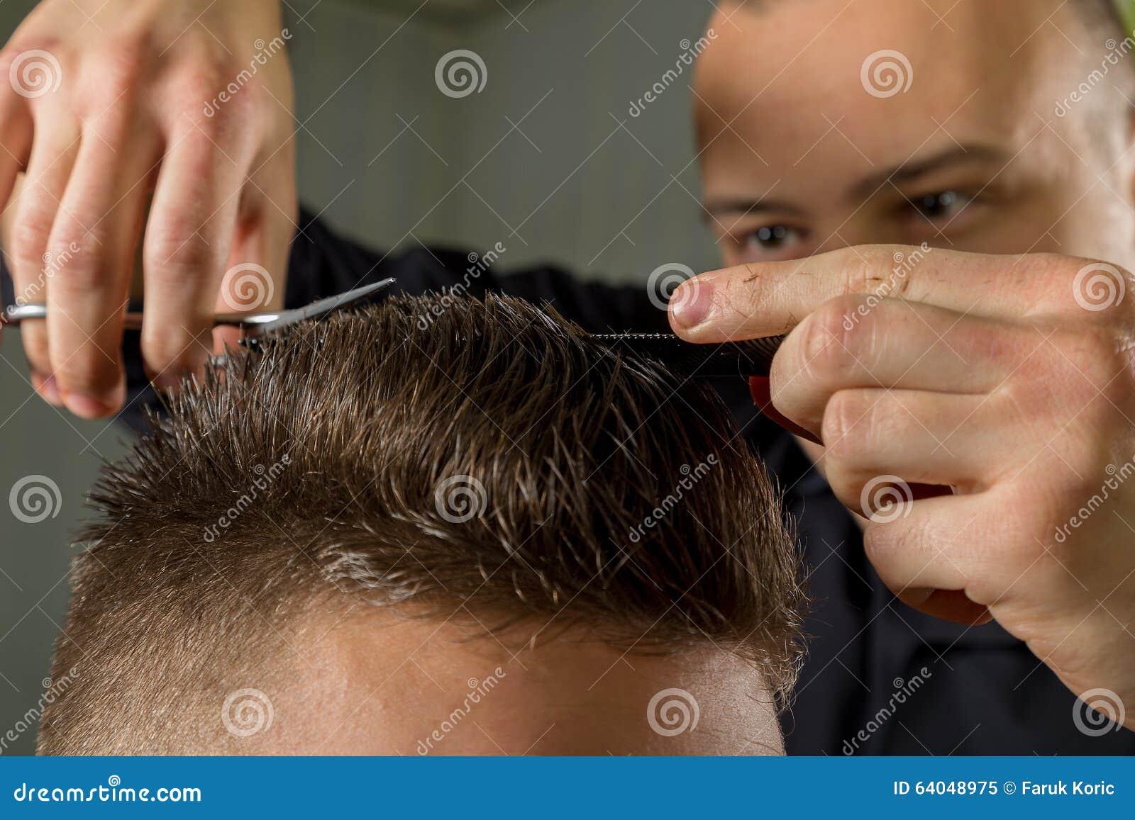 Coupe des cheveux des hommes avec des ciseaux dans un salon de beauté