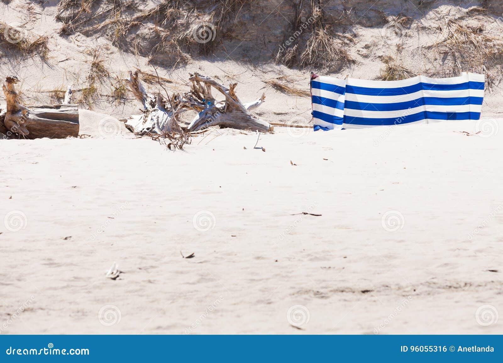 Coupe-vent bleu et blanc sur la plage sablonneuse