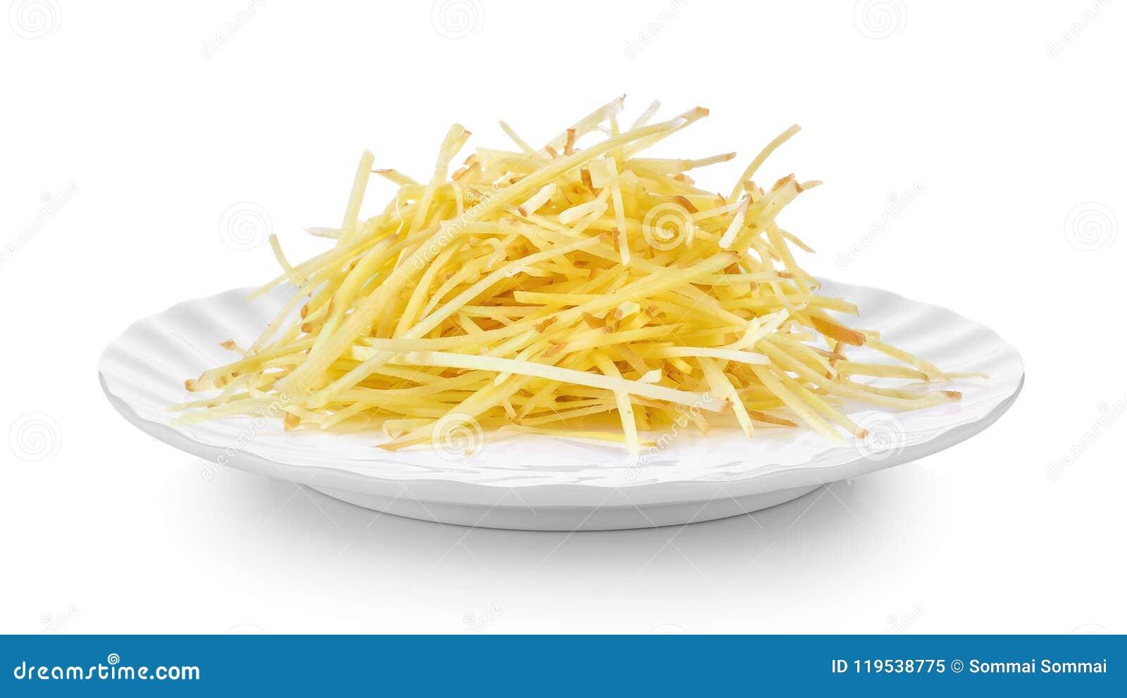 Coupez en tranches le gingembre dans le plat blanc sur le fond blanc