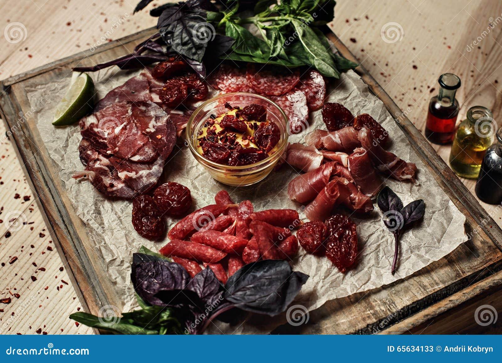 Coupez la viande sur le conseil en bois décoré du basilic
