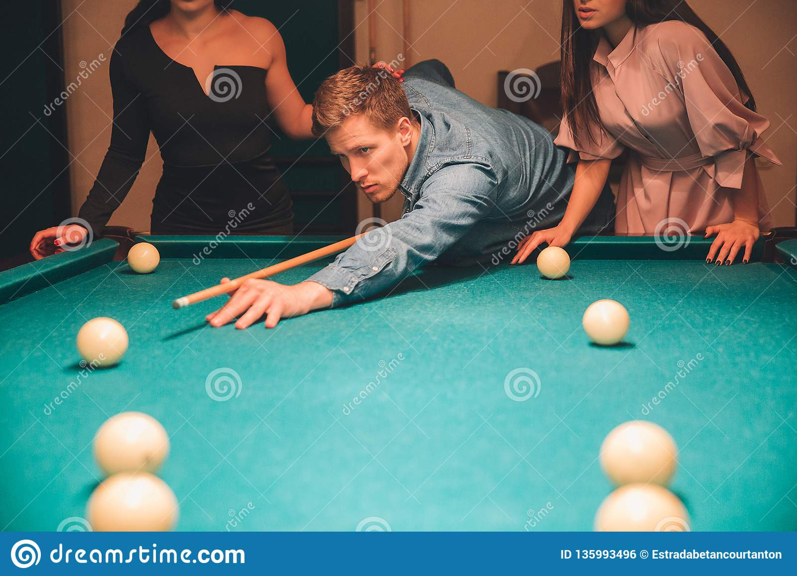 Coupez la vue du jeune homme semblant concentrée Il visant dans la boule de billard Deux modèles minces se tiennent derrière lui