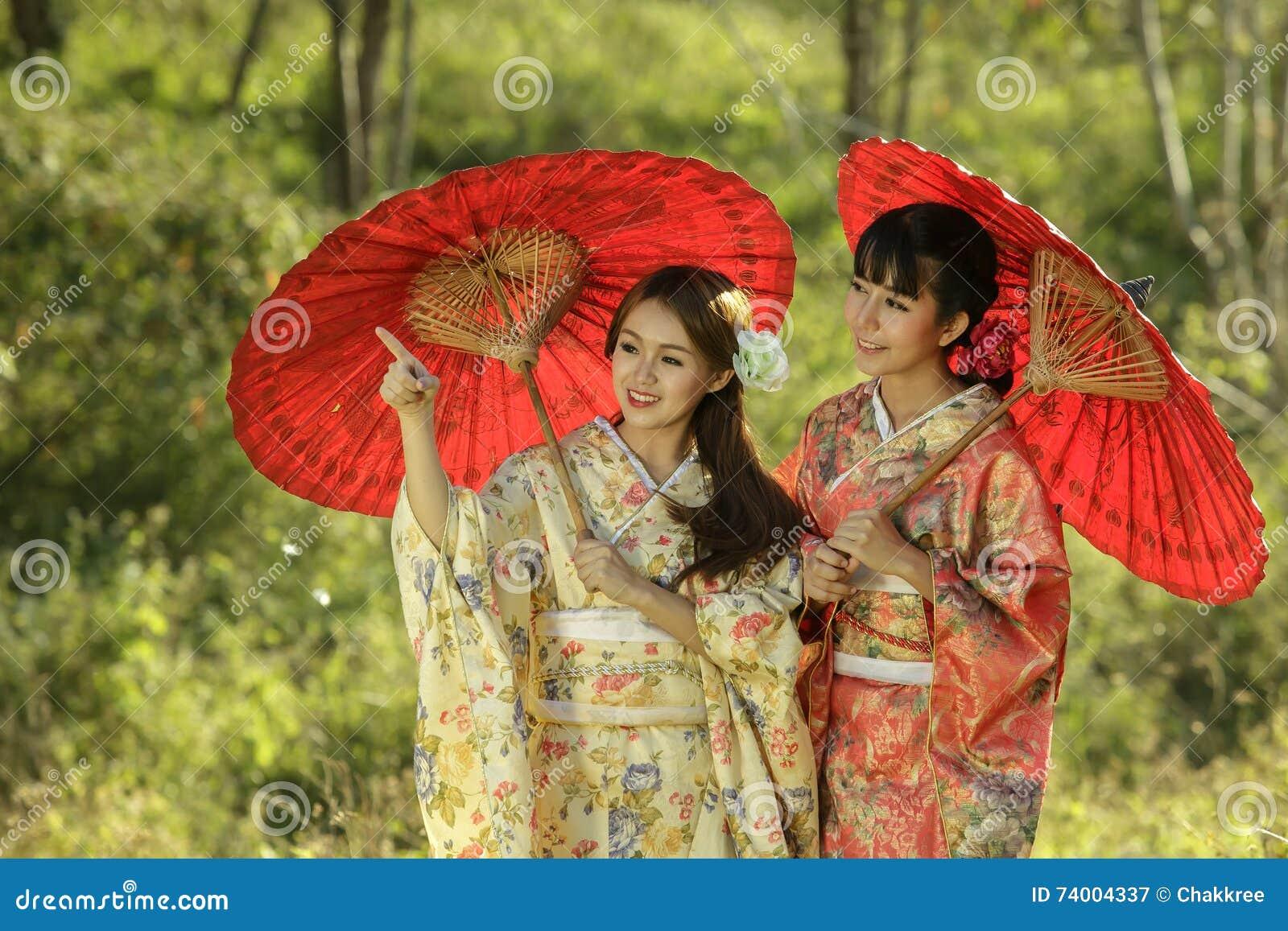 04b296ee06839 Couple asian women wearing traditional japanese kimono and red umbrella in  the himalayan sakura garden