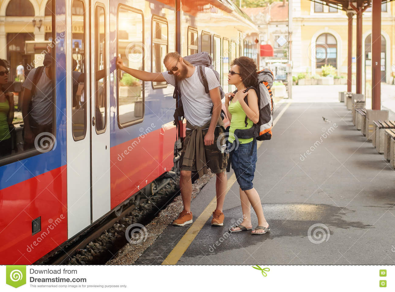A couple of backpacker tourists waiting to board a train