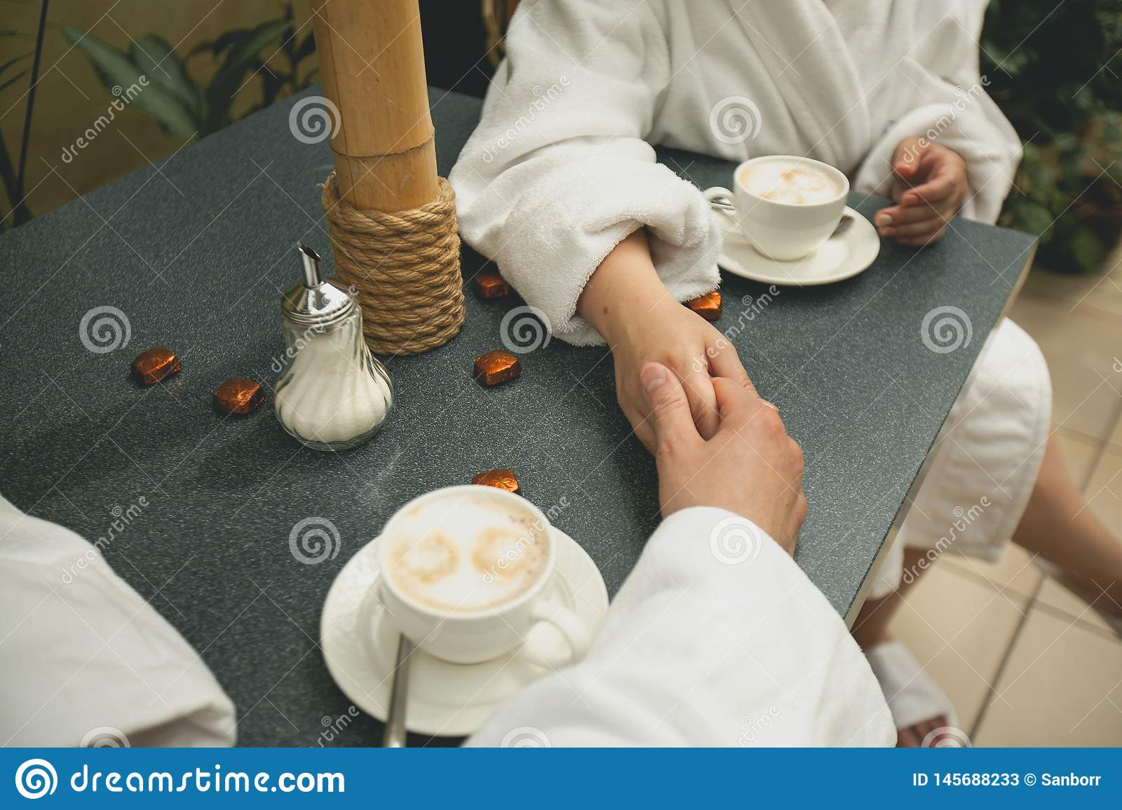A couple in bathrobes holding hands, drinking coffee while relaxing in the Spa, close-up. Hands of lovers on the background of a
