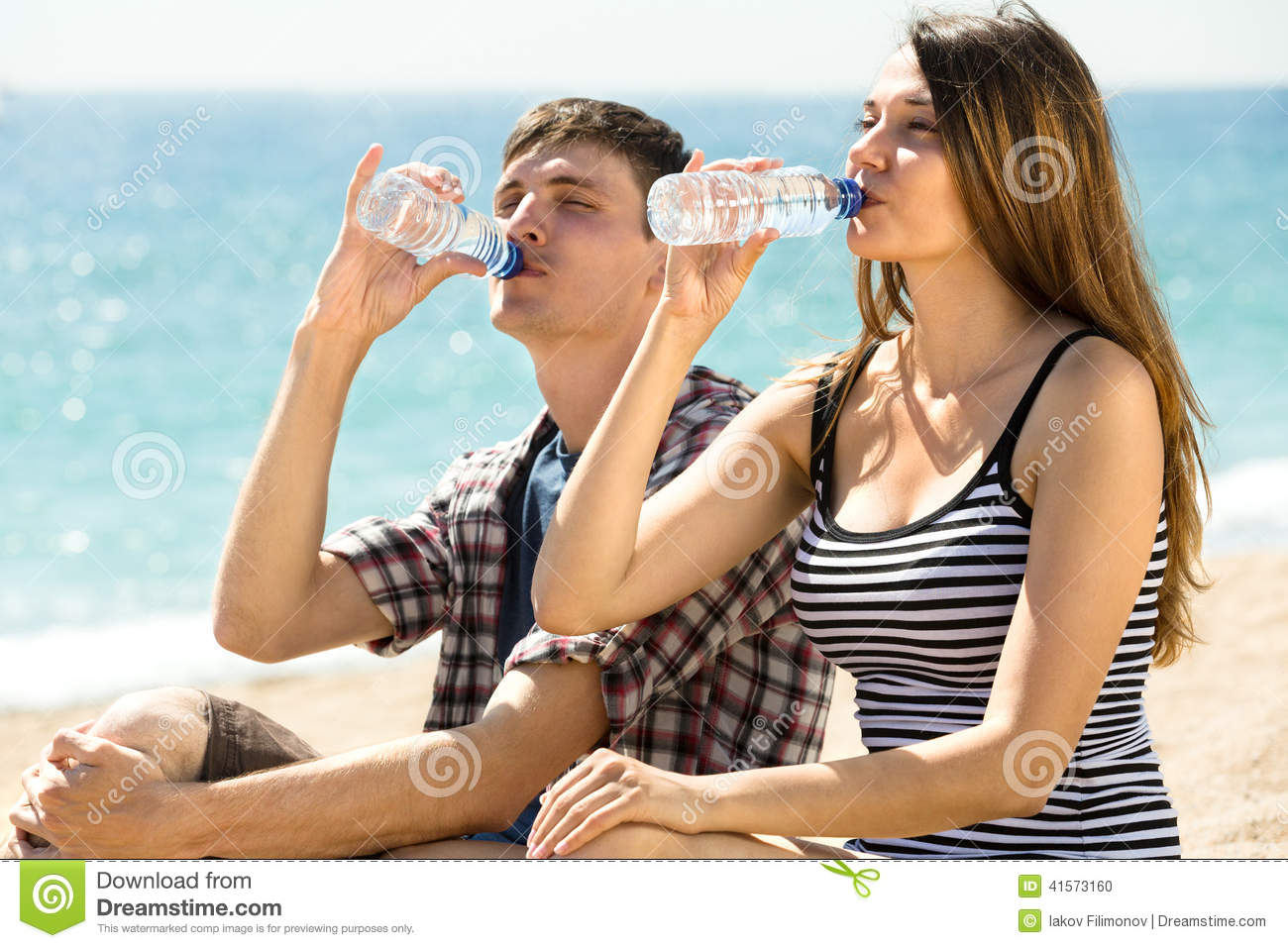 Couple on the beach drinking fresh water