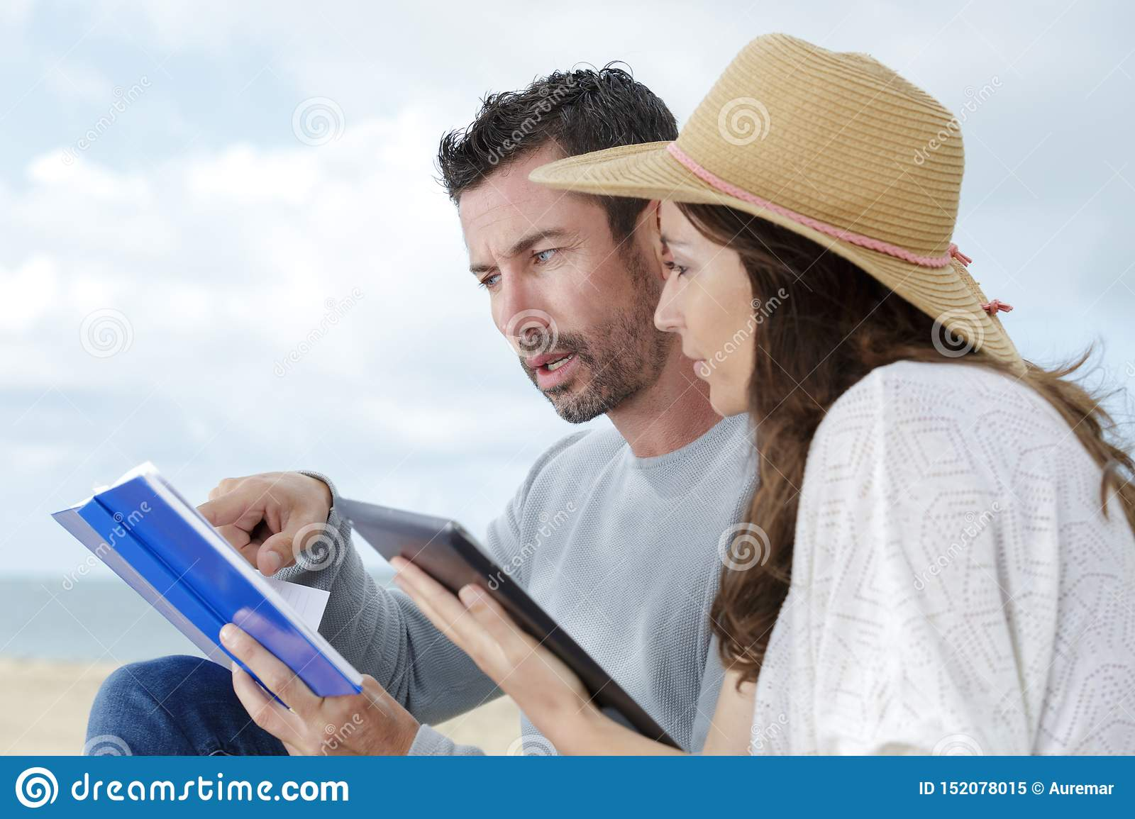 Couple on beach looking at book and tablet
