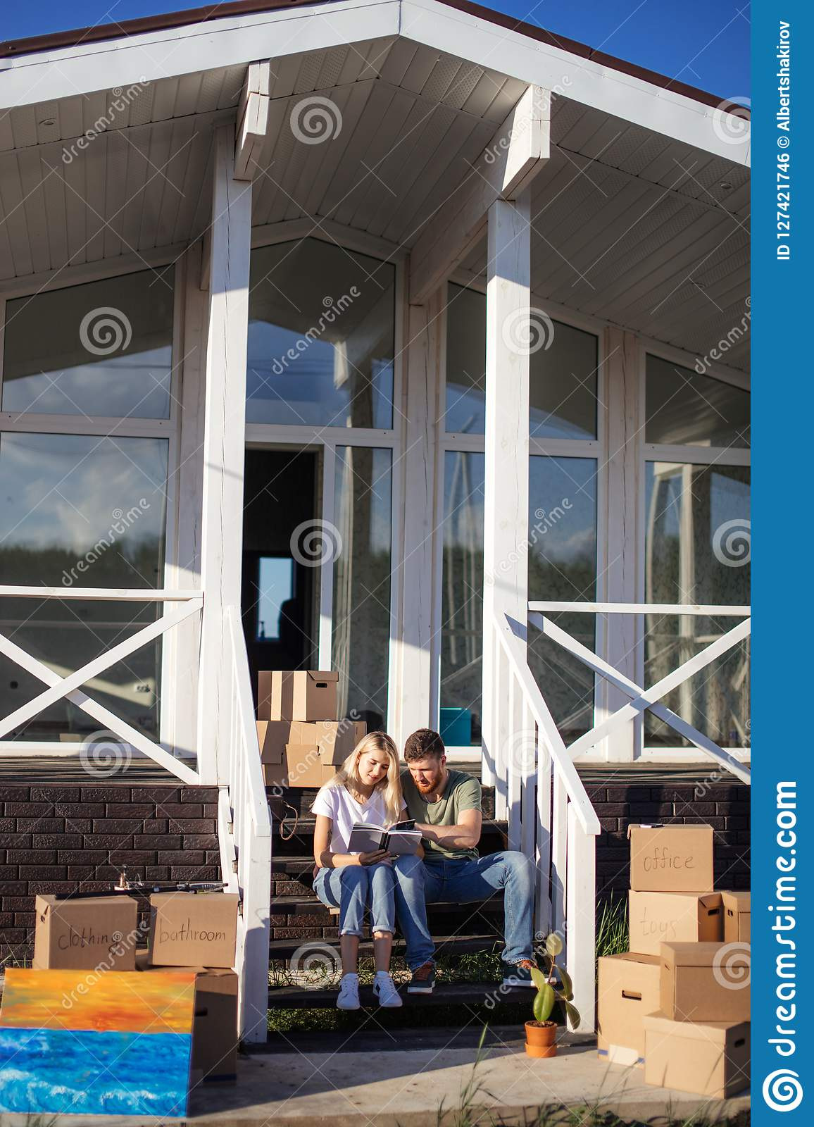 Couple With Book Sitting On Bed While Moving Into New Home Stock