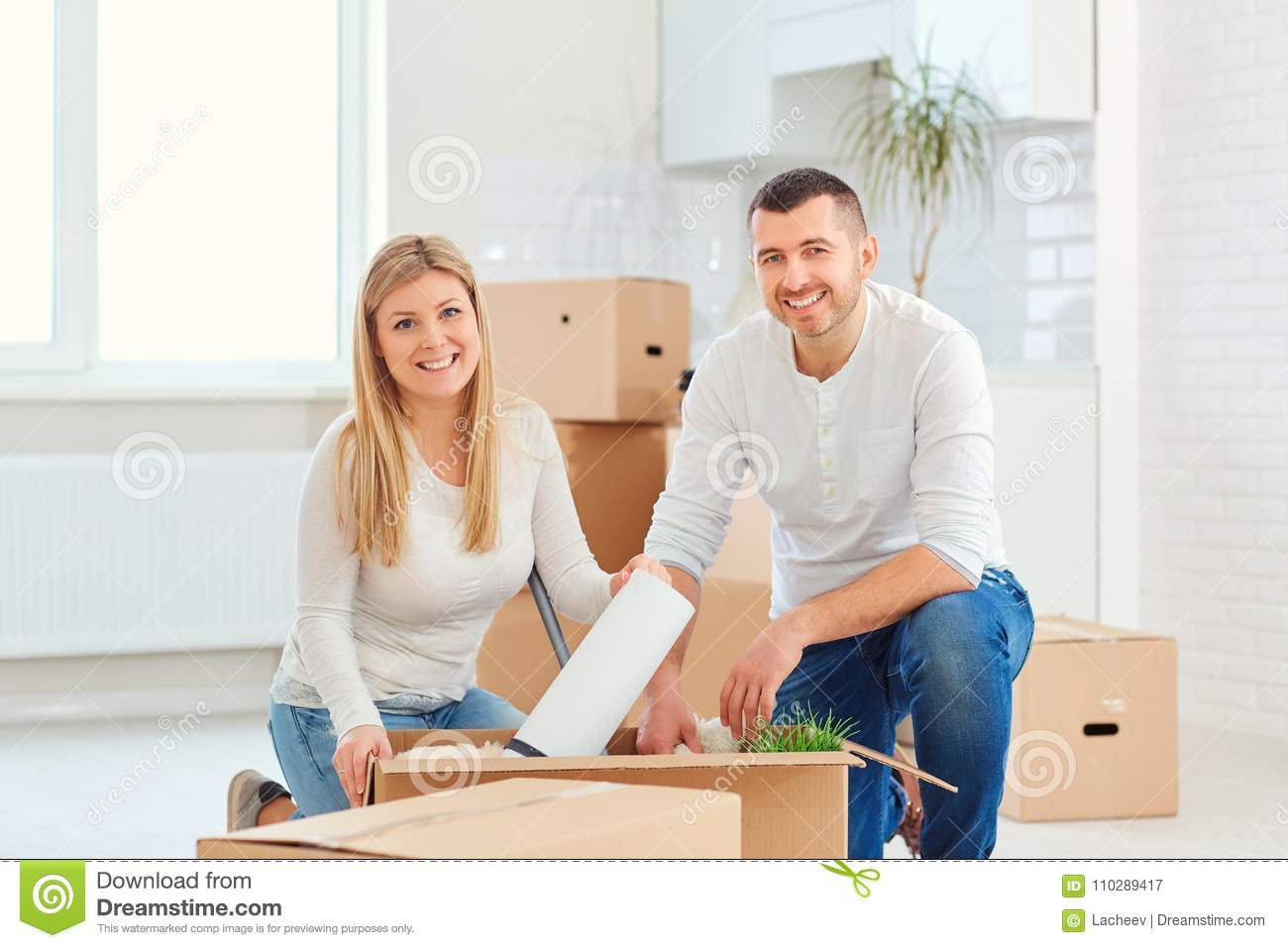 A couple with boxes moves to a new house.