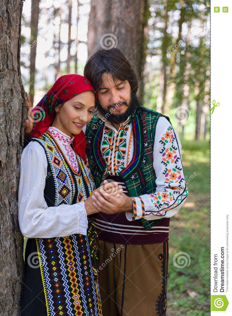 27cc026d3 Romantic couple posing in a forest wearing traditional Bulgarian clothing