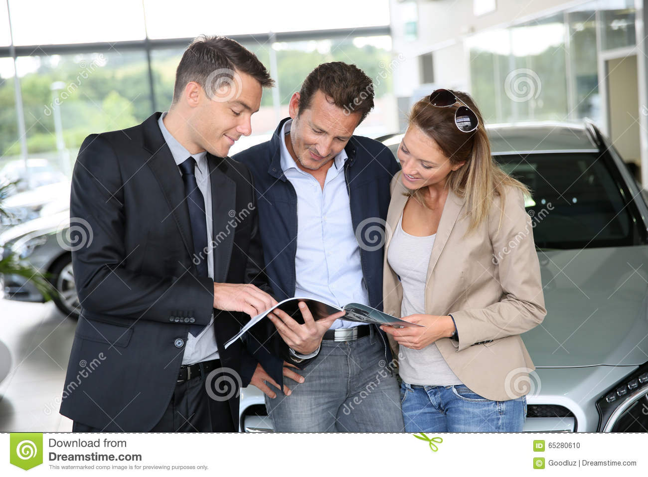 Couple buying new car with car salesman