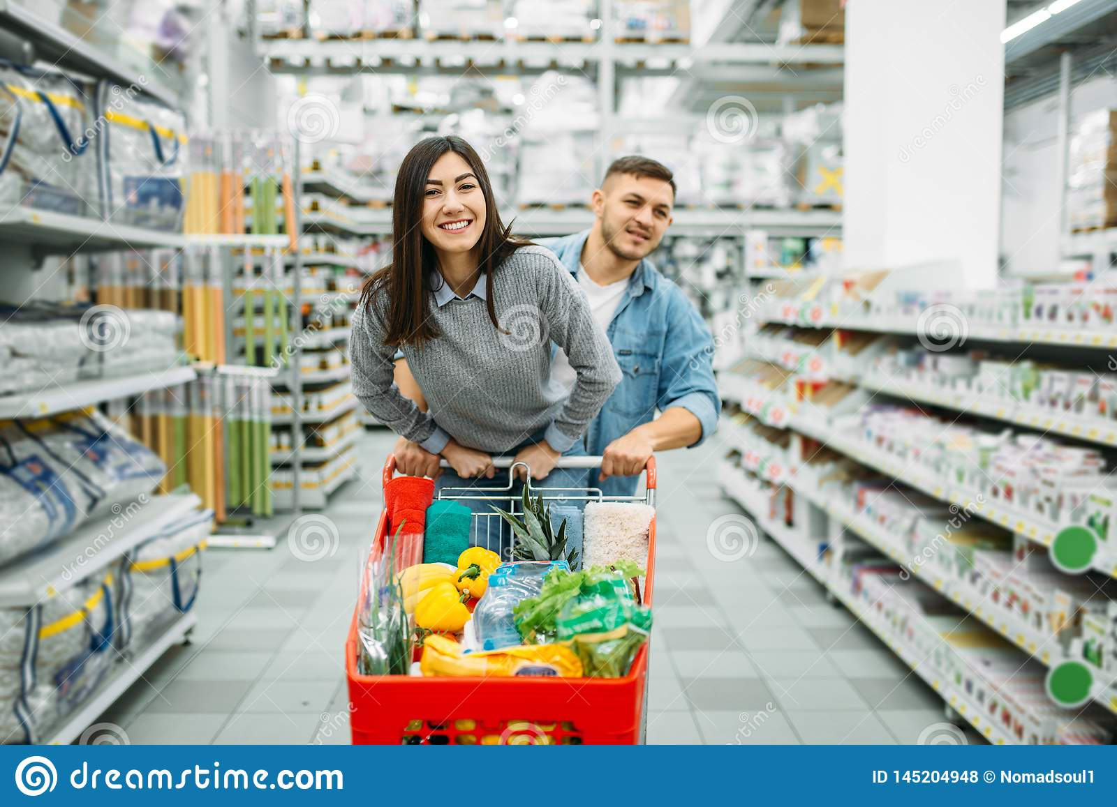 Couple With Cart Full Of Goods In A Supermarket Stock Photo