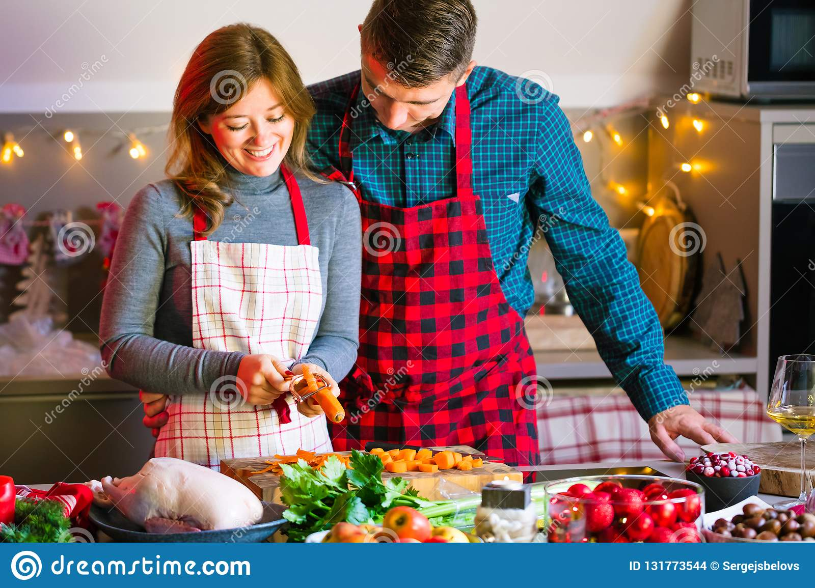 Couple celebrating Christmas in the kitchen cooking christmas duck or Goose