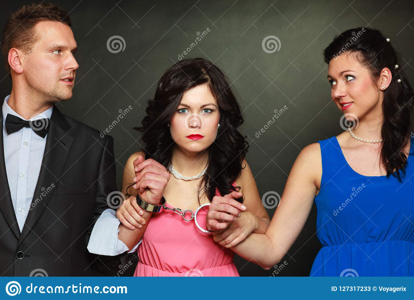 Wife and husband in handcuffs woman standing behind