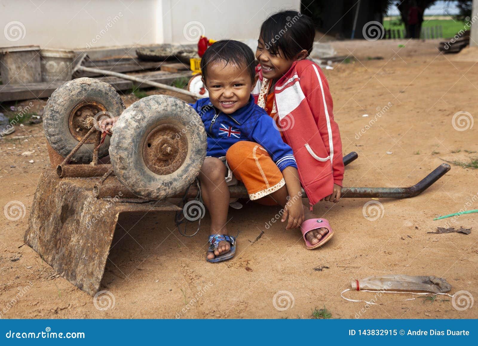 Two kids playing with a wheelbarrow