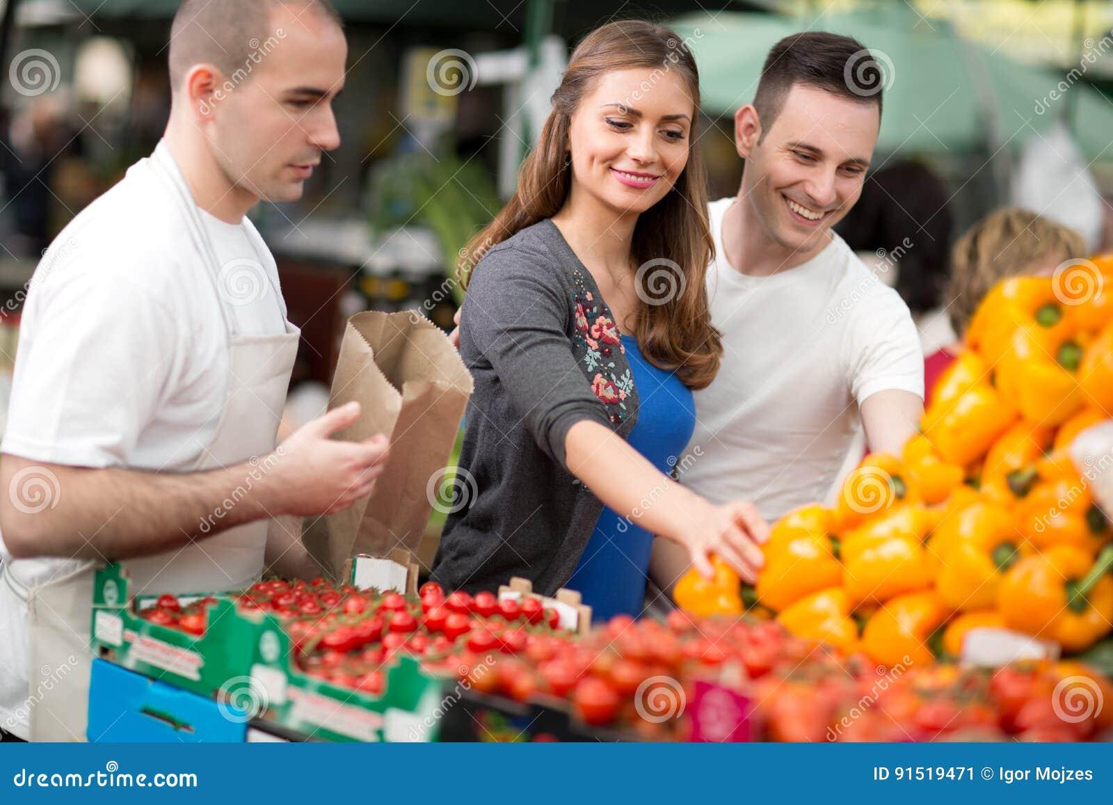 Couple choosing pepper from salesman at street market