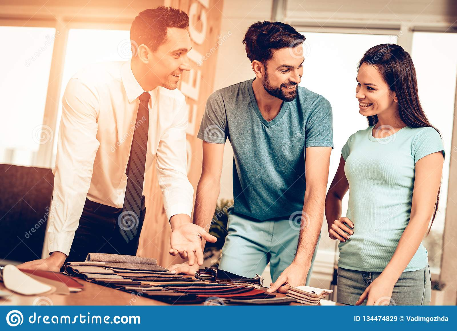 Couple Choosing Upholstery With Furniture Seller. Bright Office. Sunny Day. Professional Consulting. Colors And Patterns. Family In Store. Make A Decision. End royalty free stock images